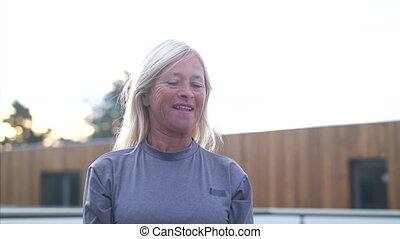 A senior woman with earphones and kettlebell outdoors doing exercise.