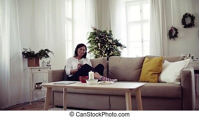 A senior woman with headphones listening to music at home at...