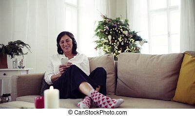A senior woman with headphones listening to music at home at Christmas time.