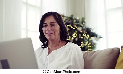 A senior woman with laptop sitting on a sofa at home at Christmas time.