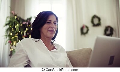 A senior woman with laptop sitting on a sofa at home at...