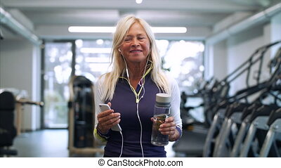 A senior woman with smartphone in gym resting after doing exercise.