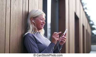 A senior woman with smartphone outdoors resting after ...