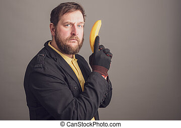 a serious bearded man in black gloves holds a banana in his hand like a pistol