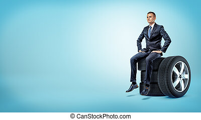 A serious businessman sitting on a stack of car tires with hands on his hips.