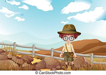 A serious explorer standing near the rocks