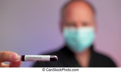 A serious man wearing protective mask showing positive ...