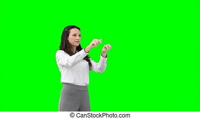 A serious woman types on a virtual keyboard
