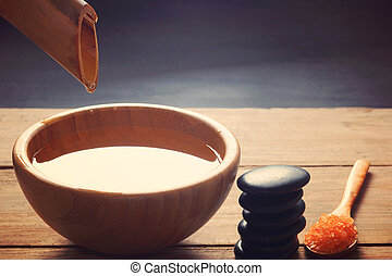 A set for spa procedures, hot massage stones, bath salts and flavored water, collected from a bamboo stem into a bowl