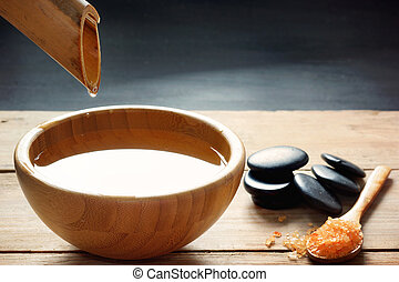 A set for spa procedures, massage stones, bath salts and flavored water, collected from a bamboo stem into a bowl