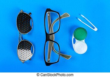 A set of accessories for sight. Medical concept. Pinhole glasses, lenses with container and glasses for sight. Top view.