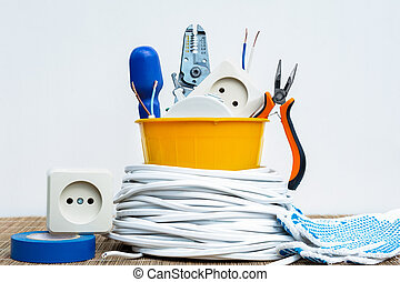 a set of an electrician in a yellow plastic pot and a wire spool