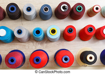 A set of coils with colorful threads in the sewing workshop.