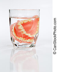 set of dentures in a glass of water - A set of dentures in a...