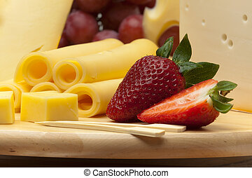 A set of different cheeses, strawberry and grapes on a...