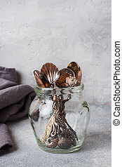 A set of different teaspoons in a glass jar. Gray background with copy space.