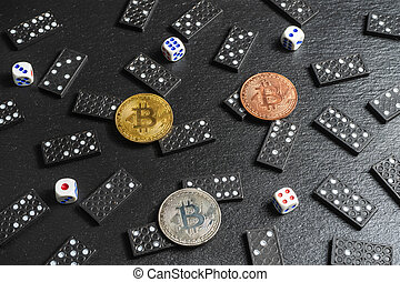 A set of domino bones, dices and bitcoins on black stone background