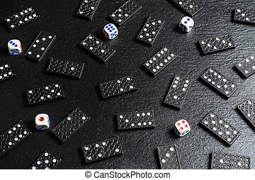 A set of domino bones, dices on black stone background