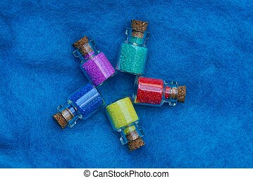 small glass decorative bottles with colored sand on blue woolen fabric