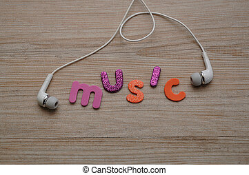 A set of head phones on a wooden background with the word music