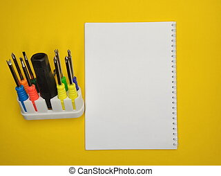 A set of multi-colored screwdrivers on a yellow background. Copy space.
