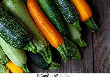 A set of multi-colored zucchini yellow, green, white, orange on the table close-up. Food background. Fresh harvested courgette, cropped summer squash. Picked green courgettes. Still life in kitchen.