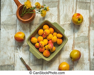 A set of nectarine and apricot fruits in a deep olive square plate on a light table, taken from the top view, a small vase with yellow meadow flowers