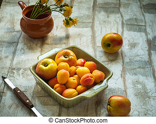 A set of nectarine and apricot fruits in a deep olive square plate on a light table, taken from the top view, a small vase with yellow meadow flowers, a kitchen knife with a wooden handle