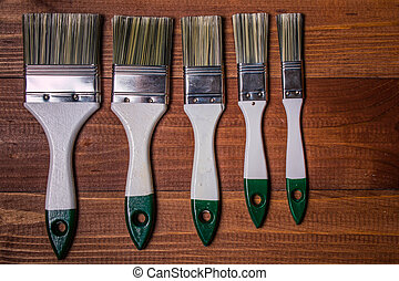 A set of paint brushes on a wooden table