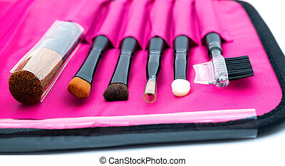 A set of professional tools for face makeup in a pink case.