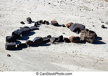 A set of rocks in the shape of a heart in the dried mud