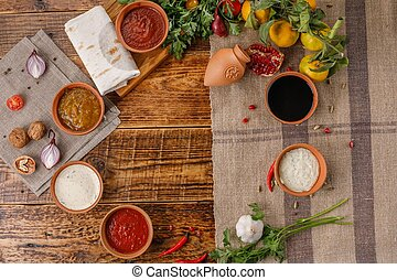 A set of sauces and condiments in ceramic cups top view.