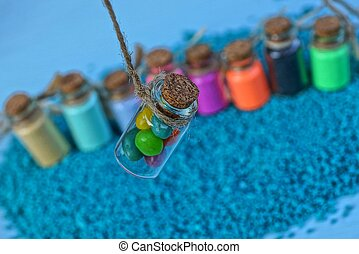 a set of small colored bottles with sand