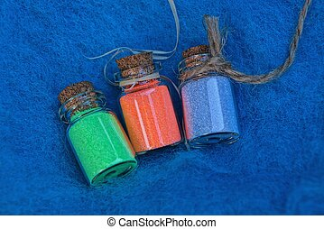 a set of small glass decorative bottles with colored sand on a blue wool fabric