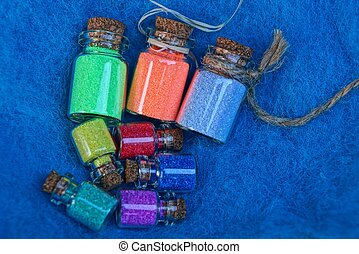 a set of small glass decorative bottles with colored sand