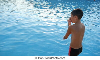 A seven year old boy jumps feet first into the sea water in summer in slo-mo