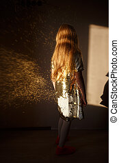 A seven-year-old girl dressed in a smart dress decorated with gold sparkles is standing in the room, the sunlight reflects from the dress and casts a glare on the wall