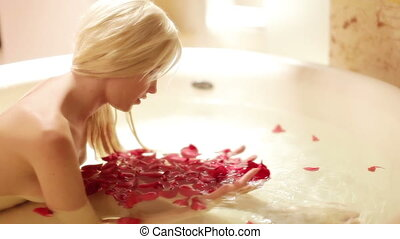 a sexy beautiful woman in a large hotel bath filled with rose petals