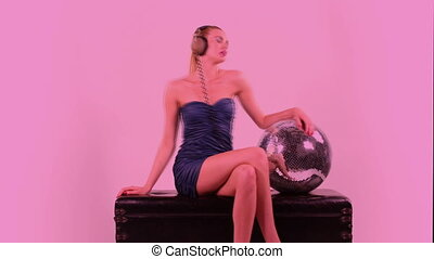 a sexy gogo dancer shot in a studio sitting and posing with a spinning disco ball.