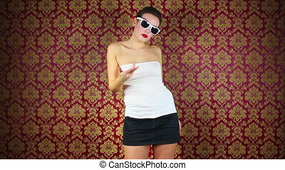 a sexy woman dances in fron of a classic wallpaper
