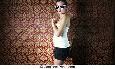 a sexy woman dances in front of a classic wallpaper background