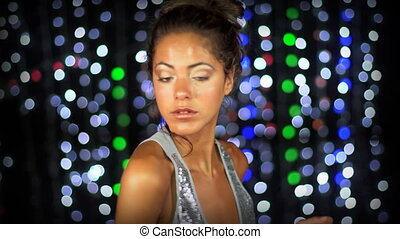 a sexy woman dances with a sparkly disco background, shot in high quality with the sony NEX-FS100
