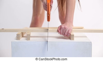 a sexy woman in a blue swimsuit sawing wooden beams with saw. the beautiful girl moves erotically.