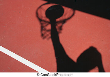 Shadow Basketball player dunking