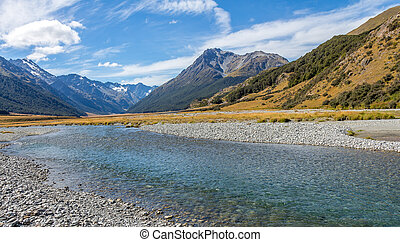 A shallow, fast flowing river, in the mountains of New Zealand on a sunny day
