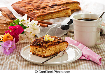 A sheet cake with cinnamon sugar butter and a hot cup of coffee