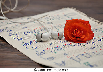 A sheet of music with earphones and an orange rose