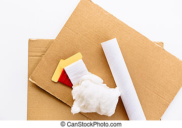 A sheets of brown cardboard, tube of paper towel, threads and wadding on a white background. Material for use in a step by step instruction for the manufacture of New Year's crafts, Christmas tree