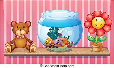 A shelf with a bear, an aquarium and a toy flower