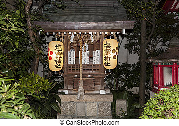 A shinto altar with lanters and praying cards.